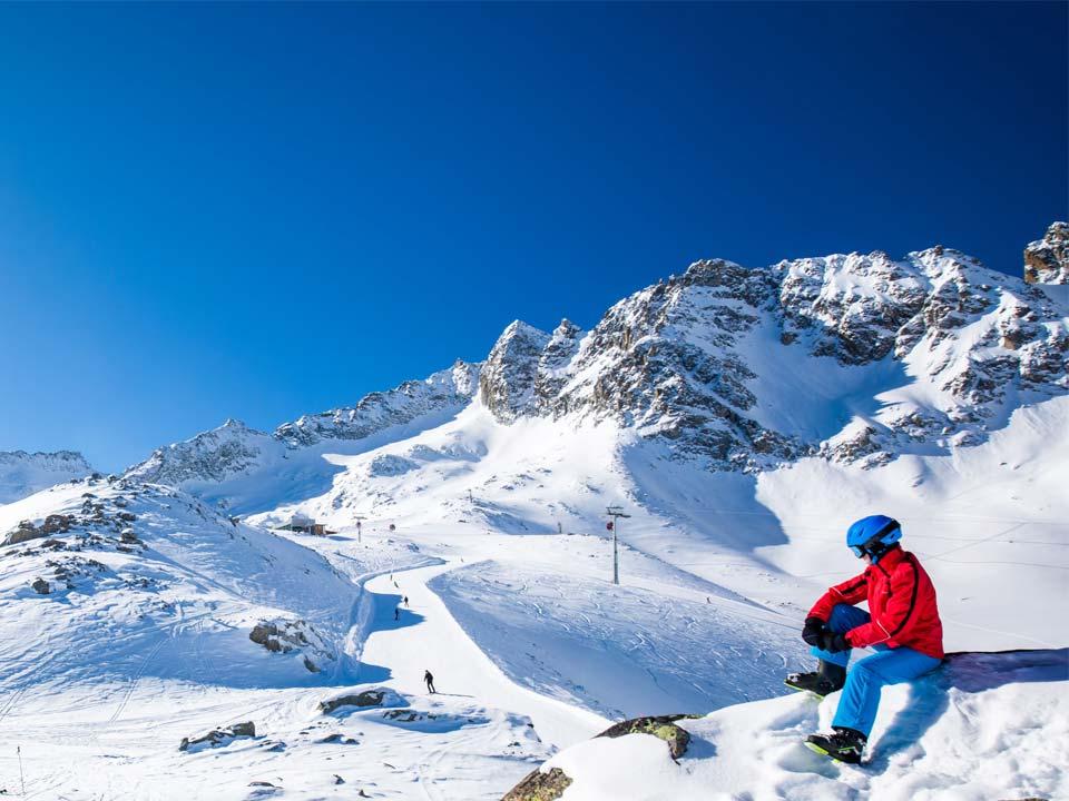 sciatore con attrezzatura noleggiata da noleggio Delpero che osserva le piste del passo Tonale